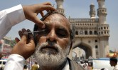 A man has his eyes smeared with traditional Kohl eyeliner before Friday prayers during the Muslim fasting month of Ramadan in the southern Indian city of Hyderabad September 5, 2008. (REUTERS/Krishnendu Halder) #