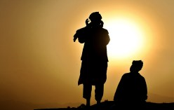 Afghan men pray on a hill