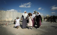 Palestinian women lead young girls through the Kalandia checkpoint, on the outskirts of the West Bank city of Ramallah, to cross to Jerusalem to attend Friday prayers at the Al-Aqsa mosques compound on September 19, 2008. Thousands of Muslim faithful have been crossing every week from the West bank to attend Friday prayers at the Al-Aqsa, Islam's third holiest shrine, since the start of the holy month of Ramadan three weeks ago. (DAVID FURST/AFP/Getty Images) #