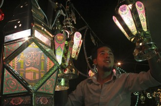 Amman, Jordan: A shopkeeper hangs decorative lights in his store in celebration of Ramadan.