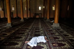 Kashmiri Muslim takes a nap at the Jamia Masjid in Ramadan