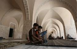 Palestinian boys read the Quran at the al-Omari mosque in Gaza City during Ramadan