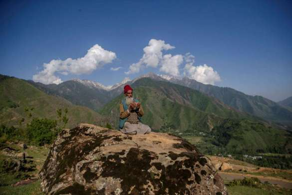 Man makes dua on a boulder in Kashmir, India.
