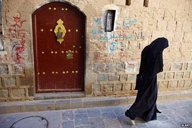 Yemeni woman walks in front of a wooden door