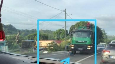 Photo of L'individu est actuellement assis au milieu de la route devant un poids lourd à Augrain