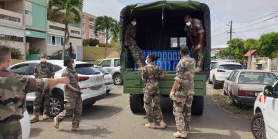 Des militaires qui distribuent des packs d'eau à Saint-James à Acajou Lamentin
