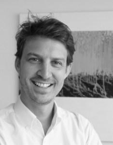 Daniel Zeisner Porträtfoto - junger Mann mit Kurzhaarschnitt und Lächeln im Gesicht, weißes Hemd in schwarz weiss