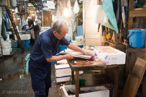 A man carving some frozen tuna at the Tokyo Fish Market