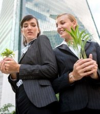 Two competitive businesswomen cupping their plants in their hands
