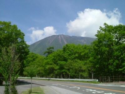 初夏の森林に囲まれた道路と山と青空