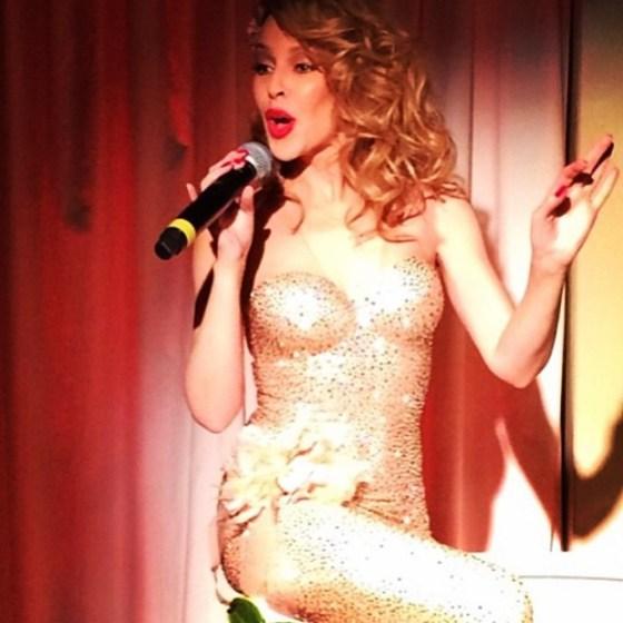 Kylie Minogue saindo do bolo na hora do parabéns