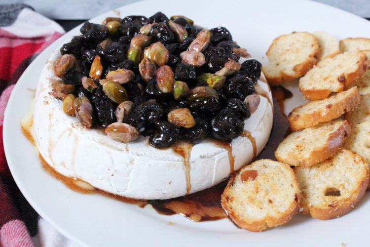 Baked Brie with Balsamic Cherries, Pistachios & Cinnamon Honey - elegant, simple and an absolute crowd pleaser, this baked brie is topped with balsamic soaked cherries, pistachios and a drizzle of cinnamon honey. Served right out of the oven it's gooey, cheesy and loaded with flavour, making it the ultimate appetizer!