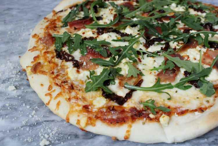 Three Cheese Pizza with Prosciutto, Sun Dried Tomatoes and Arugula - Pizza night just got tastier! An easy 15 minute homemade dough, plenty of cheese, prosciutto, sun dried tomatoes and arugula come together for the ultimate pizza.
