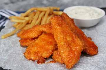 Honey Buffalo Chicken Fingers with Blue Cheese Dipping Sauce - sweet and spicy, these chicken tenders will be devoured in no time! Baked in the oven, they have a perfectly crisp outside and tender, juice inside all while being a bit healthier for you. An easy homemade blue chip served on the side pairs perfectly with these.