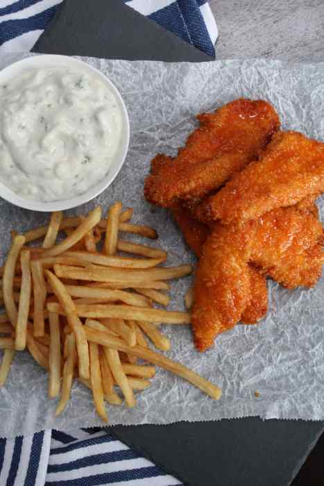 Honey Buffalo Chicken Fingers with Blue Cheese Dipping Sauce - sweet and spicy, these chicken tenders will be devoured in no time! Baked in the oven, they have a perfectly crisp outside and tender, juice inside all while being a bit healthier for you. An easy homemade blue cheese dipping sauce served on the side pairs perfectly with these.