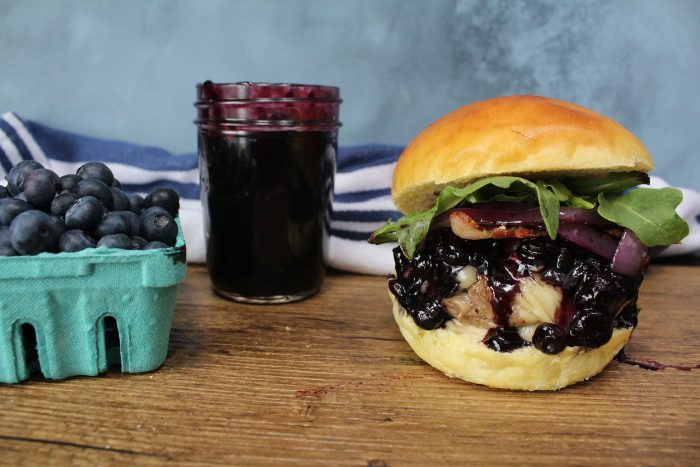Blueberry Brie Bacon Burger with a pint of blueberries and blueberry barbecue sauce
