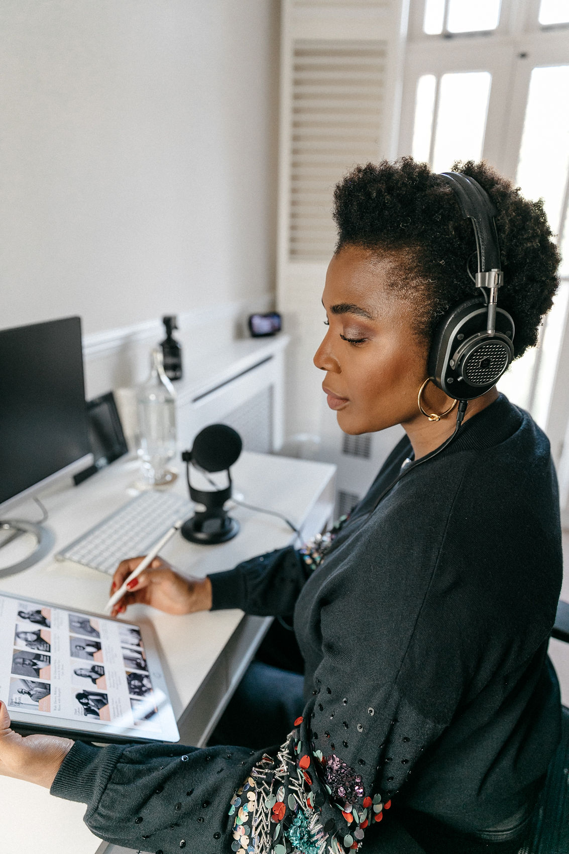 woman sitting at desk how to start a podcast master and dynamic headphone and yeti microphone