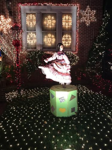 A lawn ornament shaped like a dancer in a pink dress twirling on a hexagon box; the lawn and house behind her are covered in Christmas lights