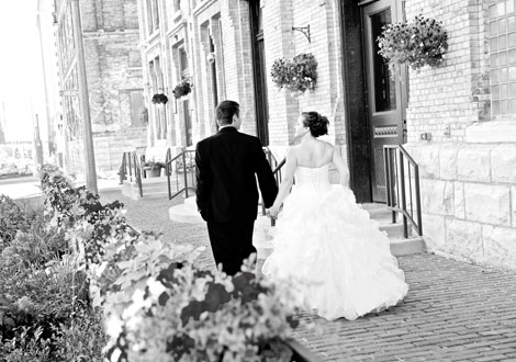 Black & white photo of the bride and groom walking down the street