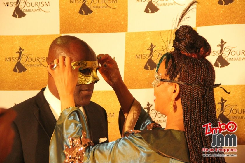 One for all and all for one! Barbara Mzembi assists the minister to put on his mask.