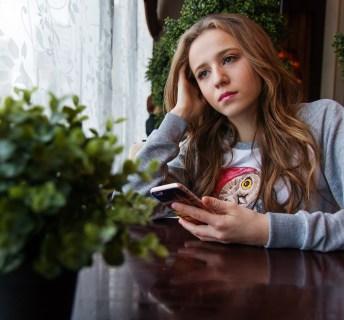 Unzufriedenes Mädchen sitzt im Wohnzimmer und schaut niedergeschlagen in die Ferne.