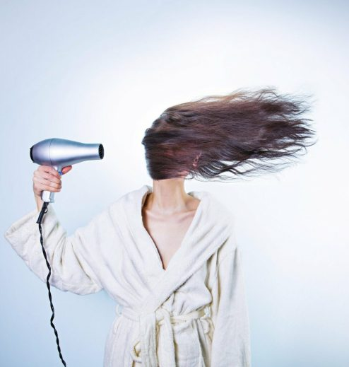 Frau föhnt ihre Haare