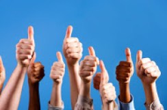 Photograph of 8 hands in the air with thumbs up.