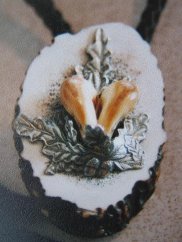 Grandln im geschnittenen Hirschhorn gefasst, mit Zinneichenlaub veredelt