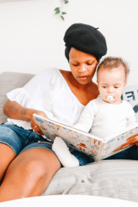 a woman reading a book with a baby. mommyonnet.com
