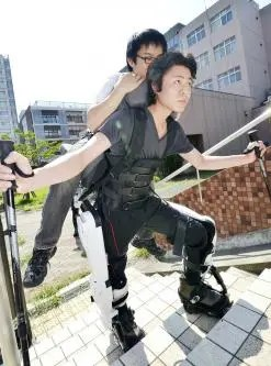 University postgraduate student Hiromasa Hara displays the Hybrid Assistive Limb climbing model, a robot suit designed to carry a person.