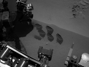 """ASA's Mars rover Curiosity used a mechanism on its robotic arm to dig up five scoopfuls of material from a patch of dusty sand called """"Rocknest,"""" producing the five bite-mark pits visible in this image from the rover's left Navigation Camera (Navcam). Each of the pits is about 2 inches (5 centimeters) wide. Image credit: NASA/JPL-Caltech"""