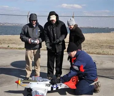 Flying a radio-controlled replica of the historic WWII P-51 Mustang red-tail aircraft—of the legendary Tuskegee Airmen—NRL researchers (l to r) Dr. Jeffrey Baldwin, Dr. Dennis Hardy, Dr. Heather Willauer, and Dr. David Drab (crouched), successfully demonstrate a novel liquid hydrocarbon fuel to power the aircraft's unmodified two-stroke internal combustion engine. The test provides proof-of-concept for an NRL developed process to extract carbon dioxide (CO2) and produce hydrogen gas (H2) from seawater, subsequently catalytically converting the CO2 and H2 into fuel by a gas-to-liquids process. - See more at: http://www.nrl.navy.mil/media/news-releases/2014/scale-model-wwii-craft-takes-flight-with-fuel-from-the-sea-concept#sthash.mM6Ly1SP.dpuf