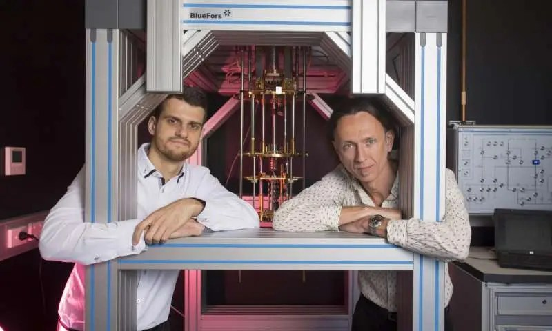 Dr. Guilherme Tosi and Professor Andrea Morello at the UNSW labs with a dilution refrigerator, which cools silicon chips down to 0.01 K above absolute zero. Credit: Quentin Jones/UNSW .