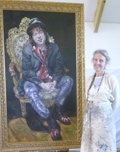 Oil portrait of a punk rocker called Buttz sitting in a high backed gold chair wearing snakeskin trousers a top hat and doc martin boots with union Jacks on them - beside the painting stands the artist Zoe Cameron in her painting apron
