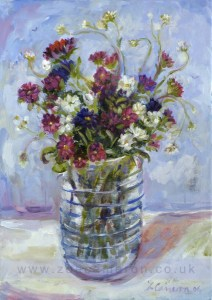 Softly painted flowers in a blue banded glass. soft blue sky and boats beyond.
