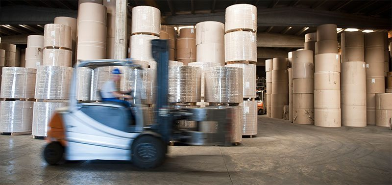 Blurred Forklift driving at speed through a paper packaging warehouse