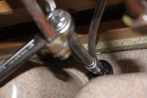 Dévisser l'écrou de maintient du mitigeur sous l'évier