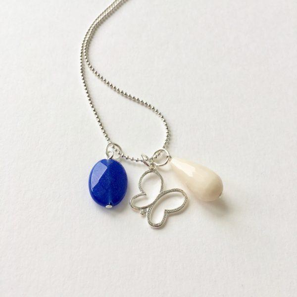 Lange ketting met blauwe en crèmekleurige natuursteen vlinder bedel zilver