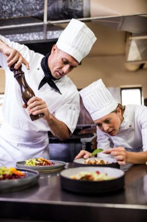 Male and female chefs preparing food in kitchen