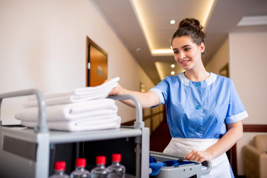 Young smiling chamber maid taking white clean towel from top of stack