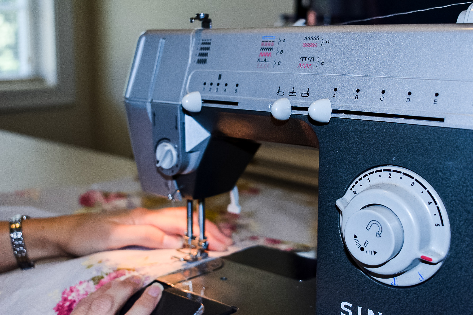 sewing machine sewing a seam on vintage floral diy button up shades