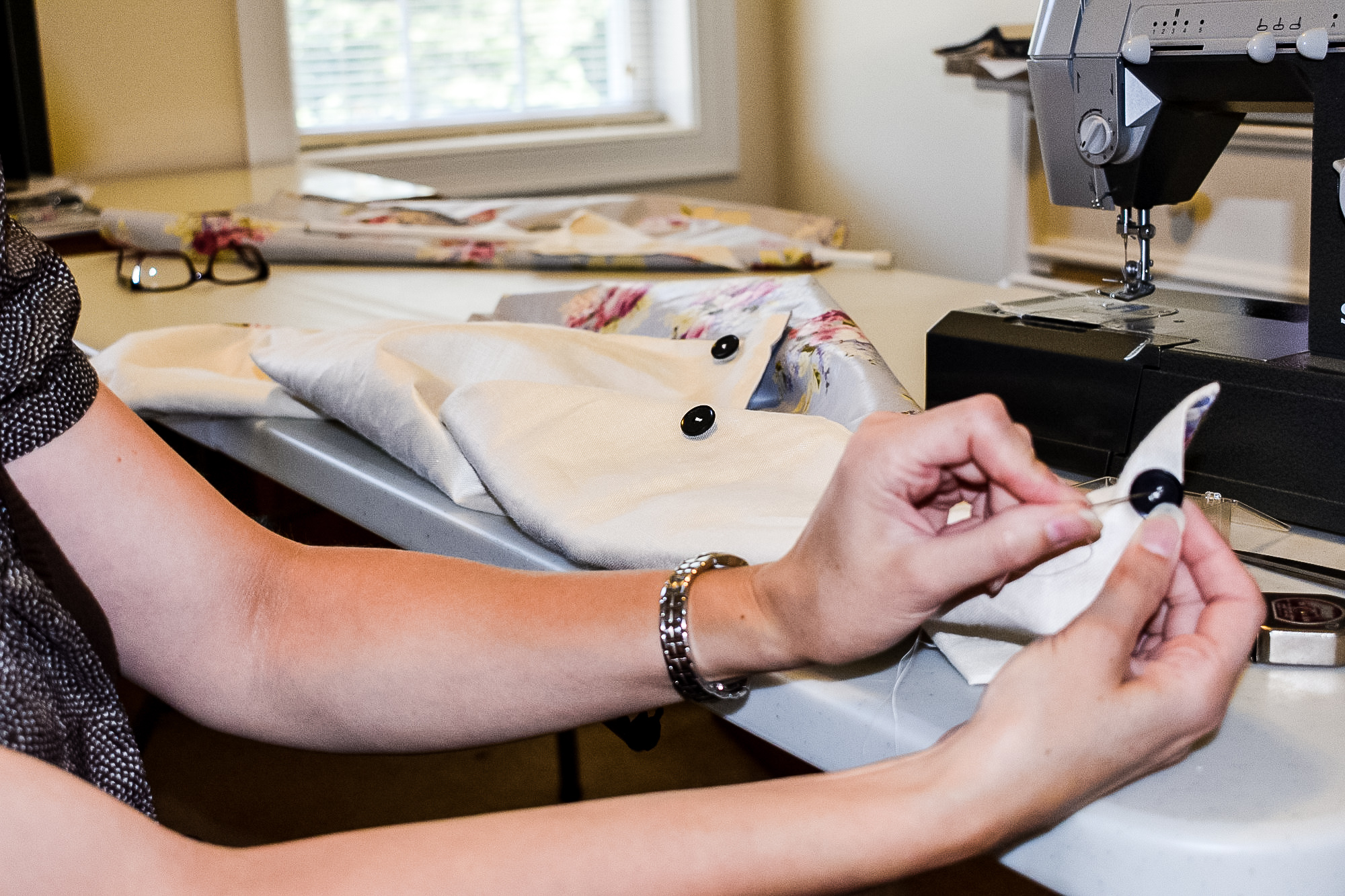 hand sewing a button onto diy button up shades