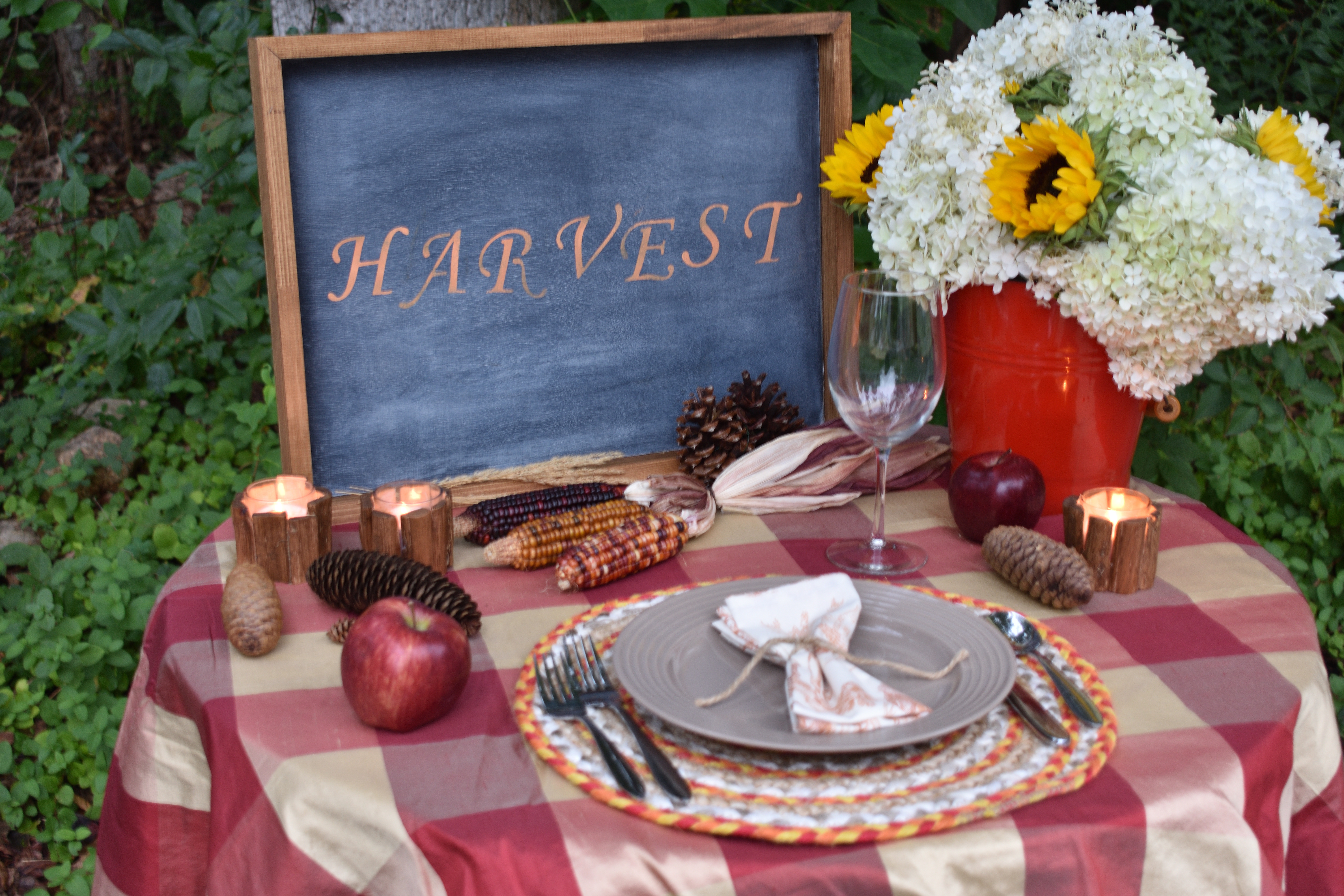 Outdoor autumn tablescape for one with a red and gold buffalo check tablecloth