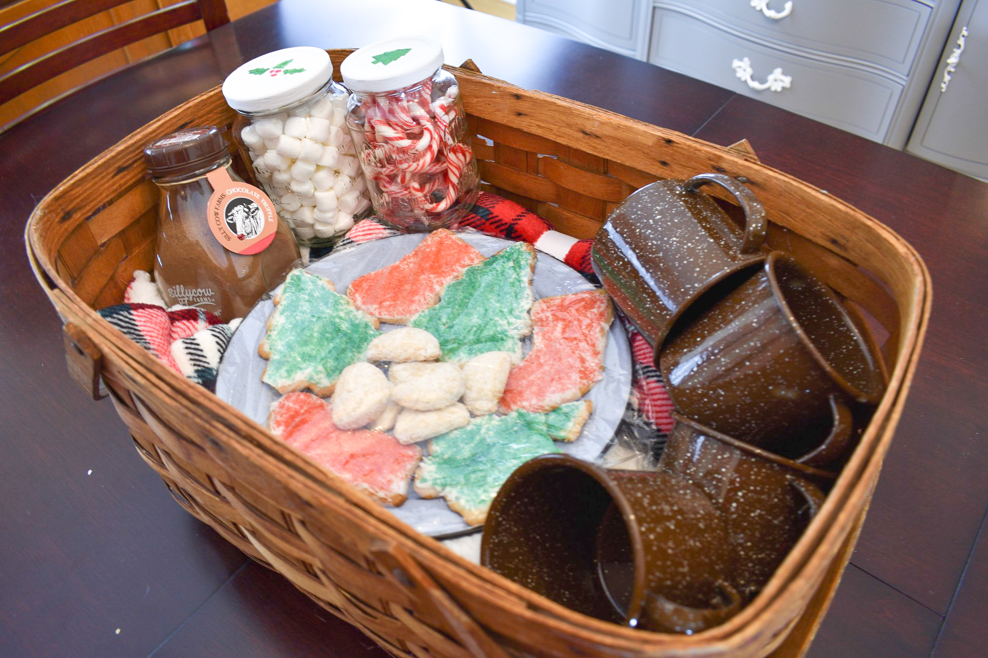 hot cocoa gift basket with a plaid throw, enamelware mugs, cookies and fixings in a vintage basket