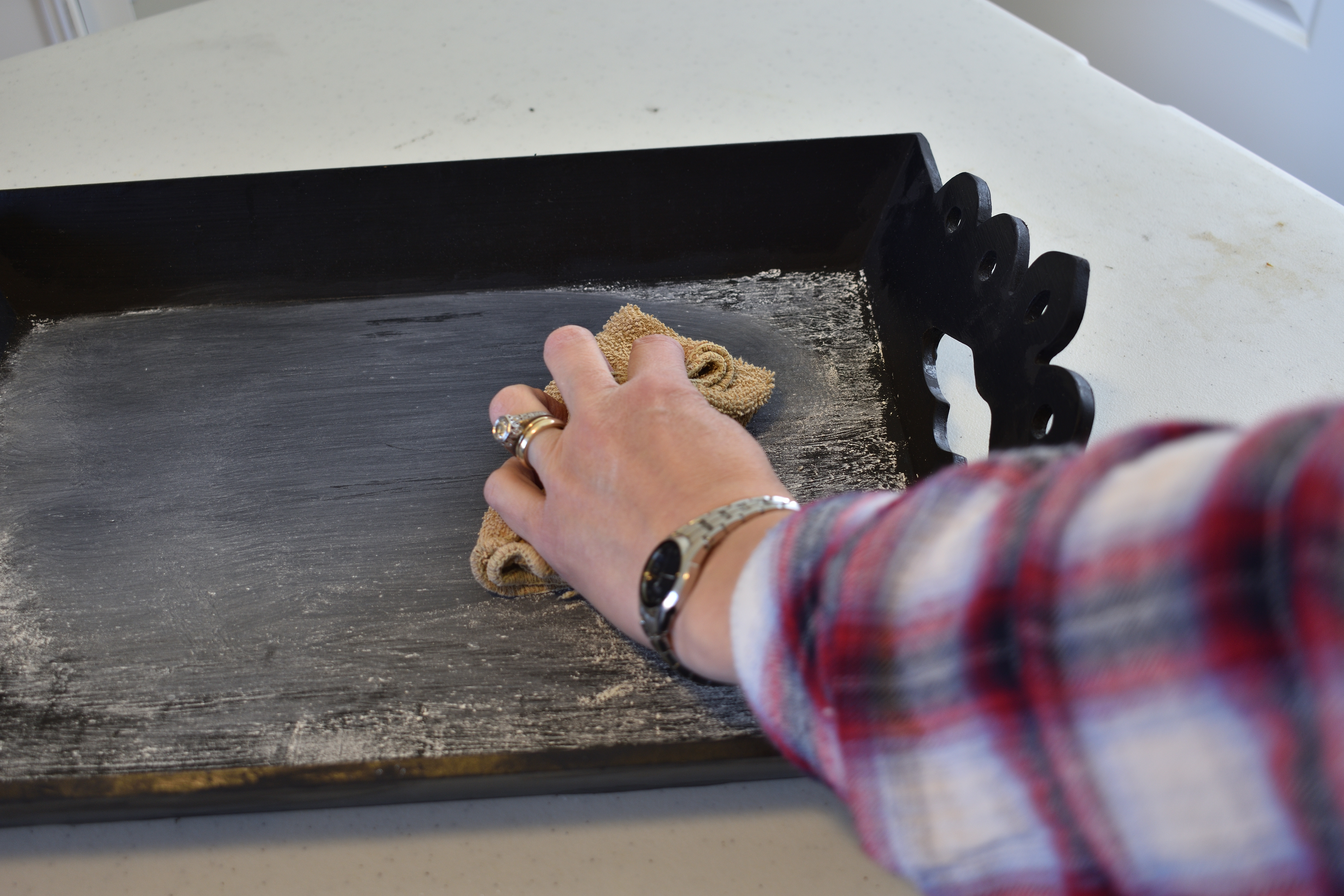 wiping the dust off of a black chalkboard tray