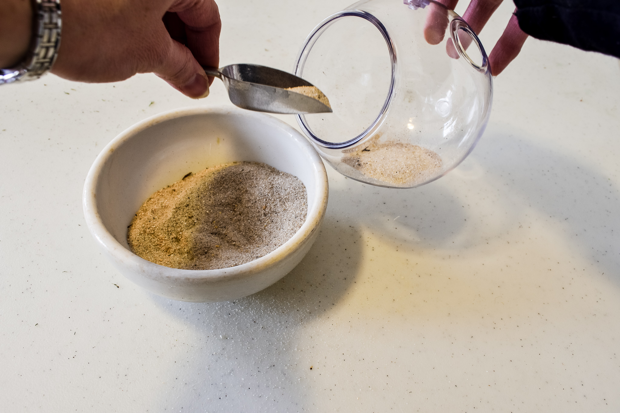 scooping sand into a terrarium to create a faux succulent decoration