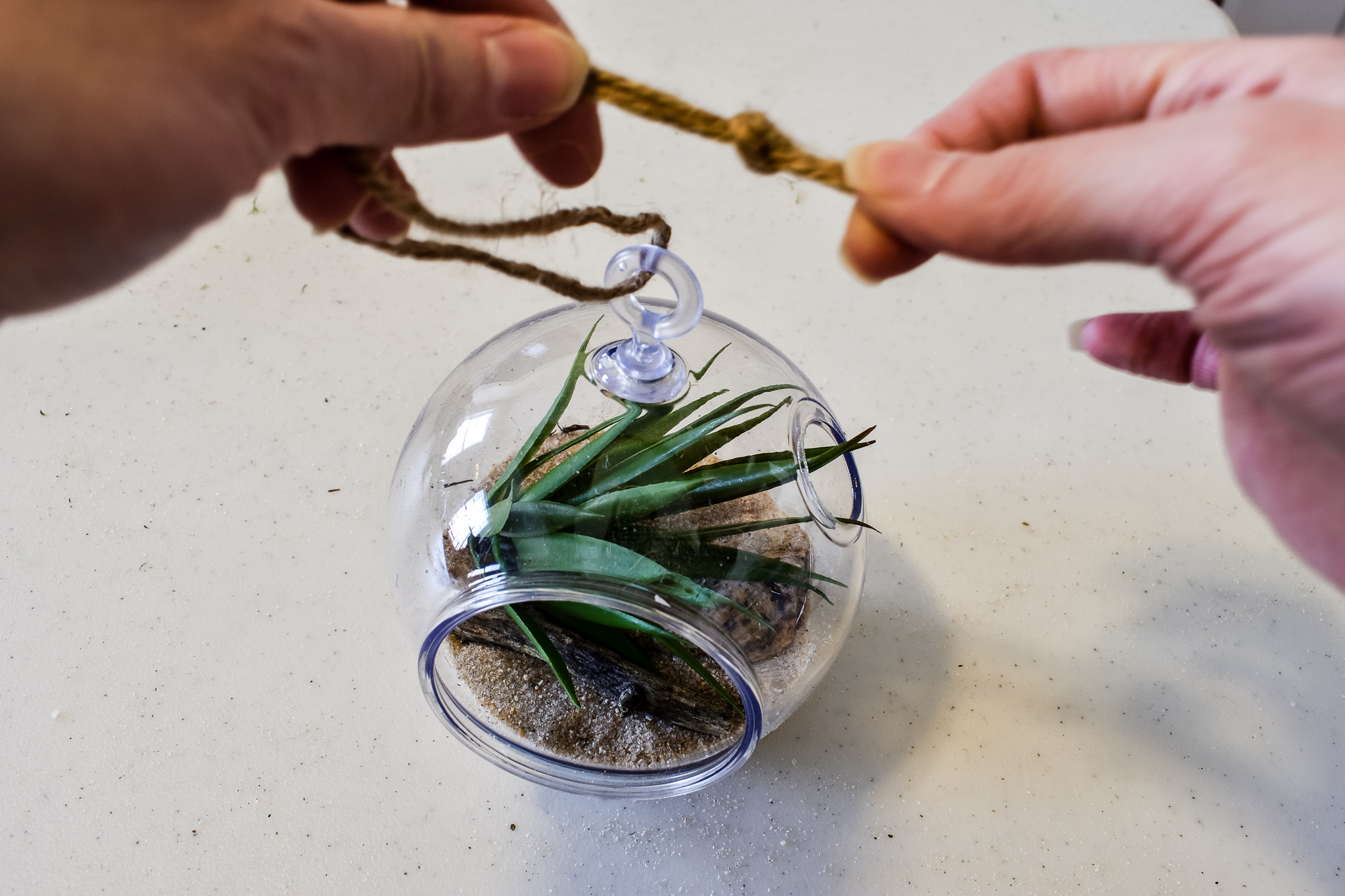 tying a jute twine hanger to the top of a faux succulent terrarium