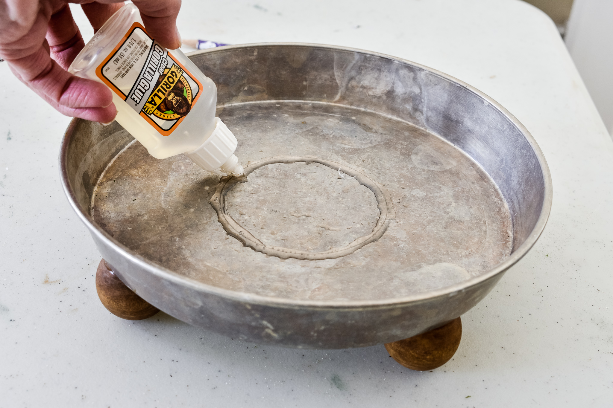 applying glue to the center of a cake pan