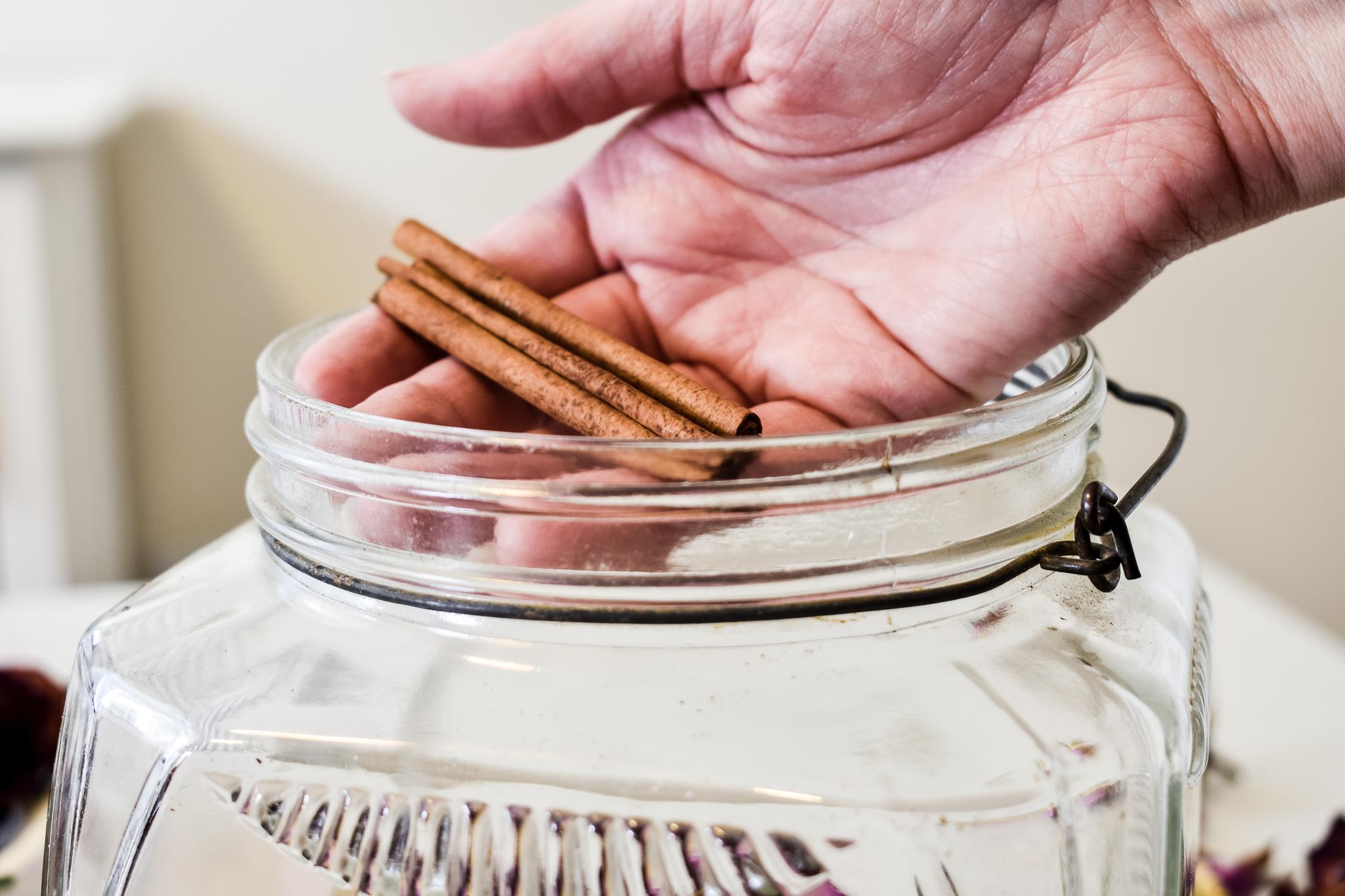 putting cinnamon sticks into a glass jar