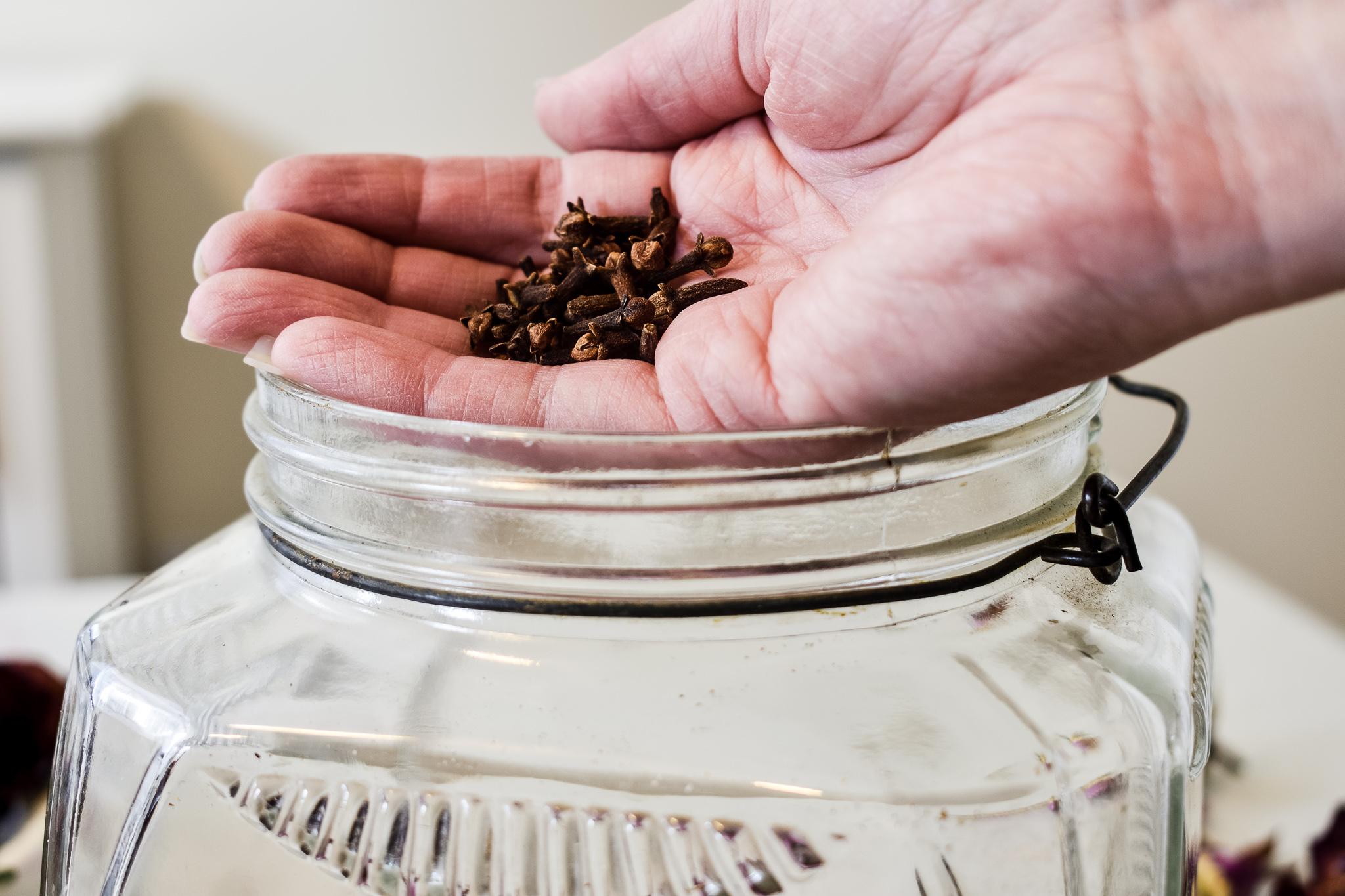 adding whole cloves to a glass rose petal jar